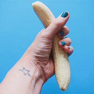 剥かれたバナナを握る女性の手